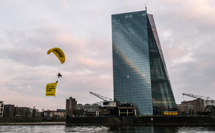 A Greenpeace protester paraglides past the ECB headquarters