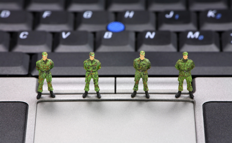 Toy soldiers on keyboard representing cyber security