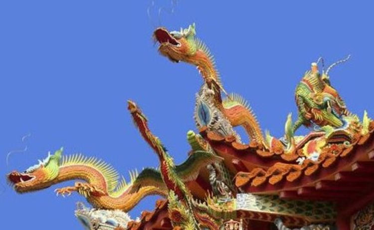 chinese-dragons-three-on-gate-top-orange-against-blue-sky